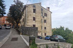Zgrada s parkingom na usponu za stari grad s niskim zidićem